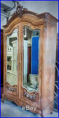 Antique French walnut armoire, ca 1890 with carved double bewelled mirrored doors